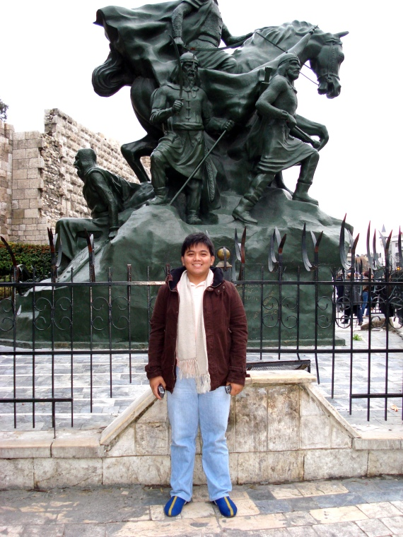 in front of a statue of Saladin